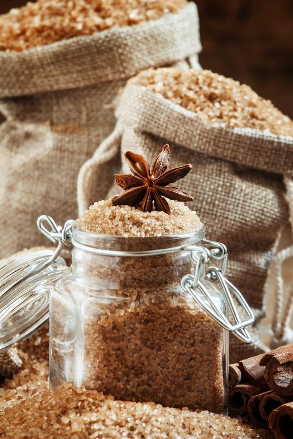 Brown cane sugar in bags made of burlap and a glass jar with a s stock images