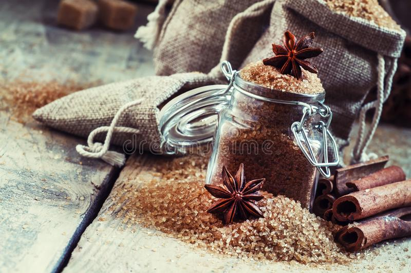 Brown cane sugar in bags made of burlap and a glass jar with a s stock photos