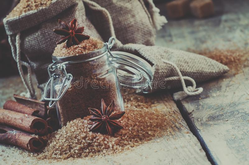 Brown cane sugar in bags made of burlap and a glass jar with a s royalty free stock image