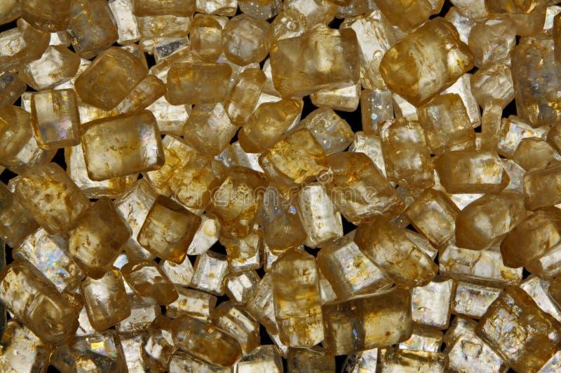 Brown cane sugar crystals in polarized light. Brown cane sugar crystals close up. Full frame shoot. Polarized light, crossed polarizers royalty free stock photos
