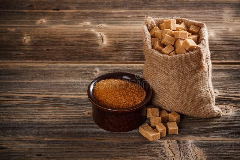 Brown cane sugar. Cubes in burlap sack royalty free stock photos