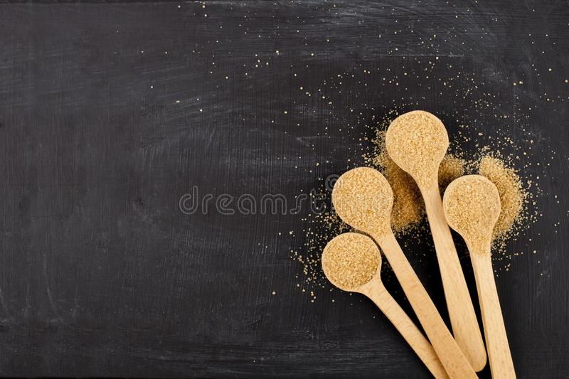 Brown cane sugar in four wooden spoons on black background stock photos