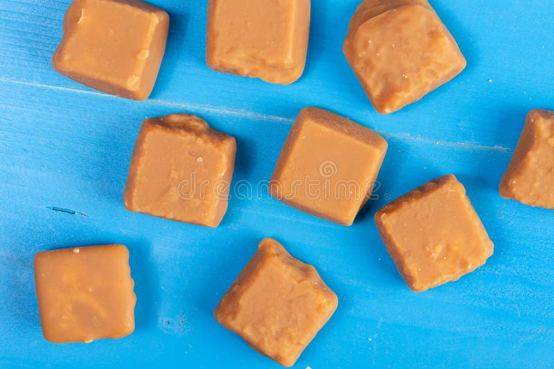 Brown Caramel Candies On The Blue Wooden Boards royalty free stock images