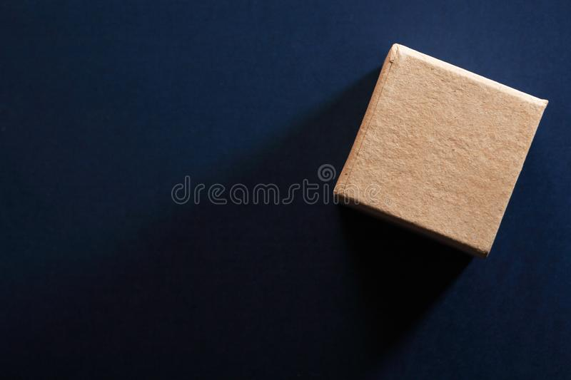 Brown Cardboard Cube. One brown cardboard cube on dark blue background stock image
