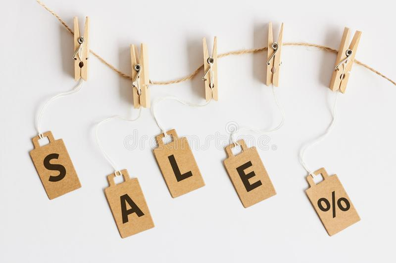 Brown cardboard price tags with sign sale hanging on wooden clothes clips on white background. Top view royalty free stock photo
