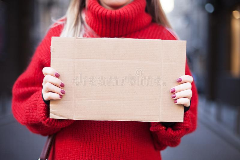 A brown cardboard tablet in the hands of a girl in a red sweater on the city street. Empty space for the layout. Mock up royalty free stock photos
