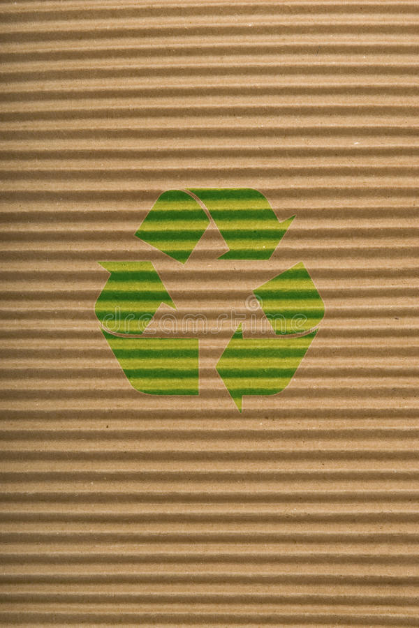Brown cardboard texture and recycling sign. Brown corrugated cardboard texture, striped horizontally paper and green recycling sign royalty free stock photos