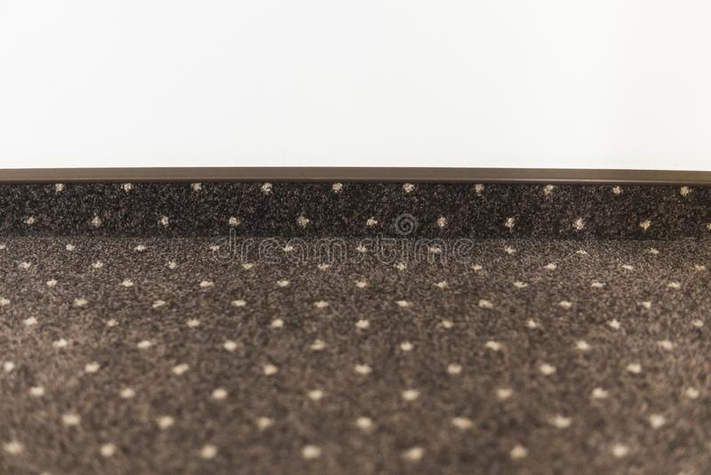 Brown carpet floor with a white dots with a carpet baseboard on a white wall. stock photography
