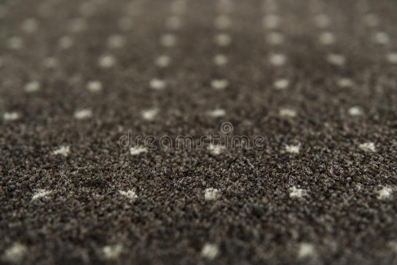 Brown carpet with a white dots texture. Indoor carpeting shoot in daylight. stock images