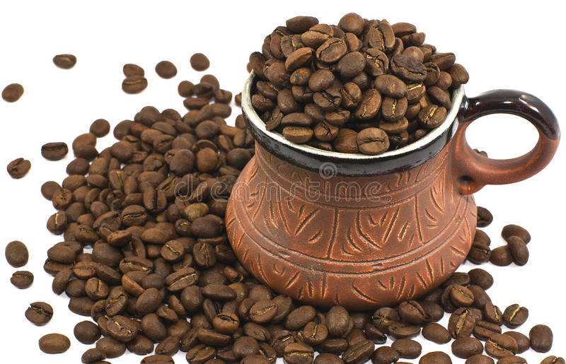 Brown ceramic coffee cup filled with coffee beans stock photo