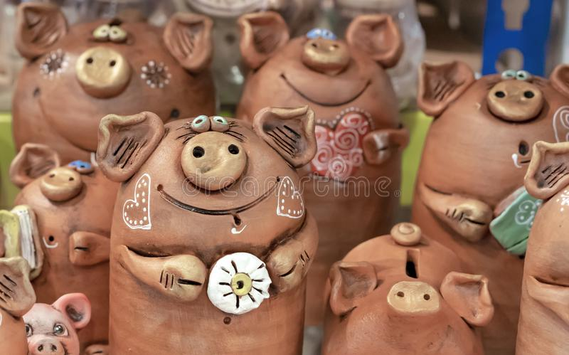 Brown ceramic piggy banks with painted hearts stock images