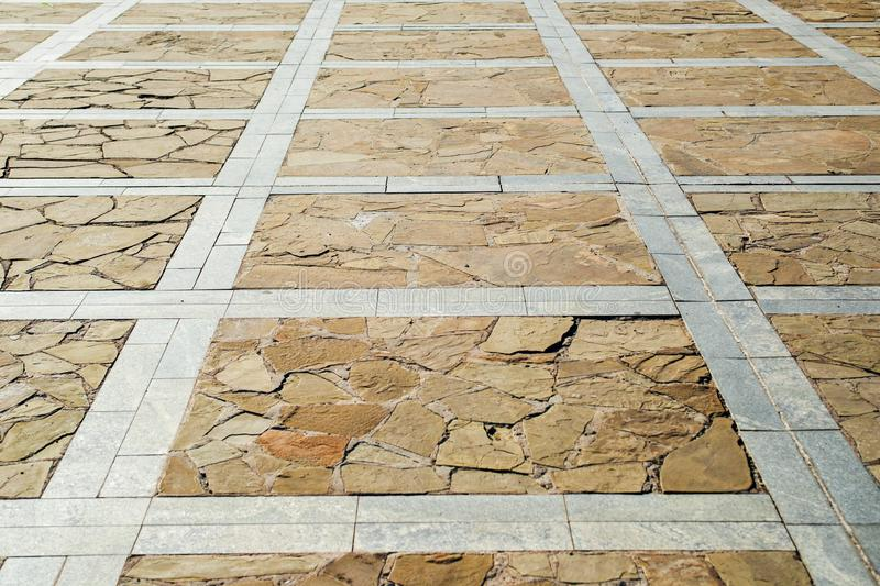 Brown ceramic tiled floor background. Large area, paved with stone tiles. Background. Texture stock photography