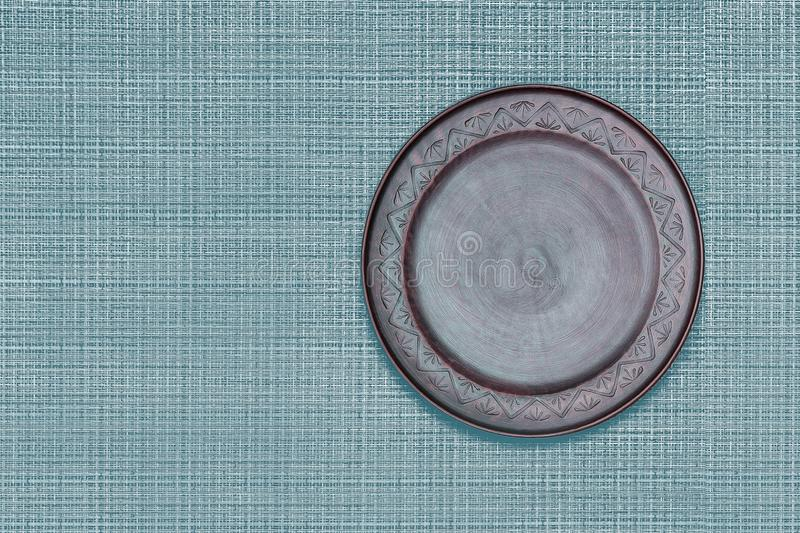 Brown ceramics dish plate on blue classic color bamboo mat. royalty free stock images