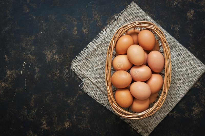 Brown chicken eggs in a basket on a dark rustic background, copy space, top view. royalty free stock photography