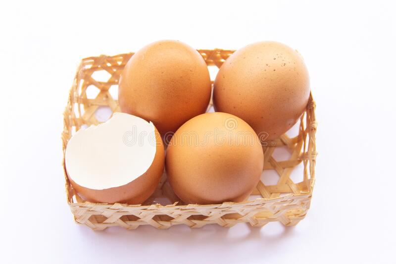 Brown chicken eggs are placed in bamboo trays. With an eggshell on a white background stock images