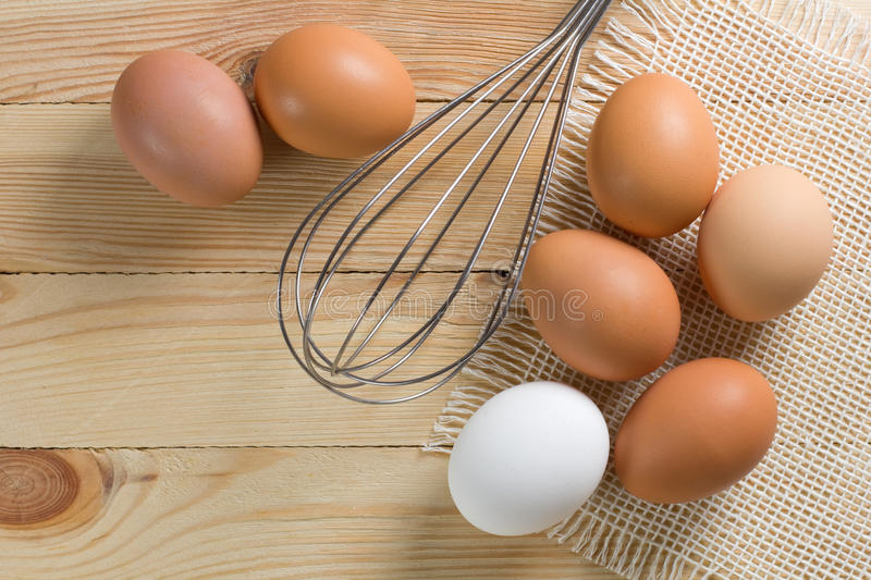 Brown chicken eggs with whisk on the wooden table royalty free stock photography