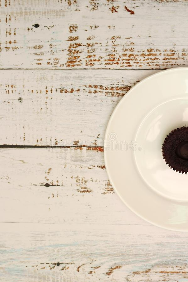 Brown chocolate cupcakes with cream filling on a white plate on the table with shabby boards stock image