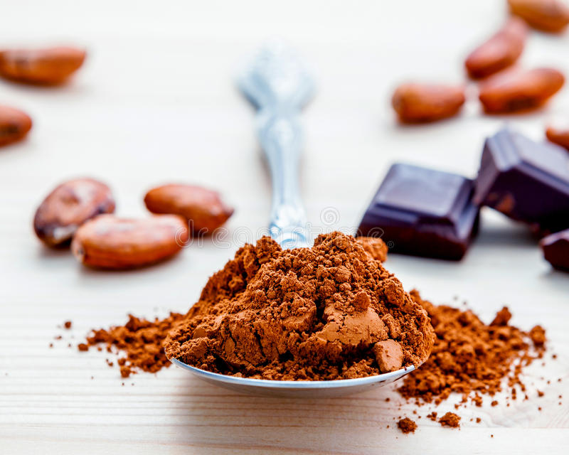 Brown chocolate powder in spoon , Roasted cocoa beans and dark c. Hocolate setup on wooden background. Selective focus depth of field on chocolate powder stock images