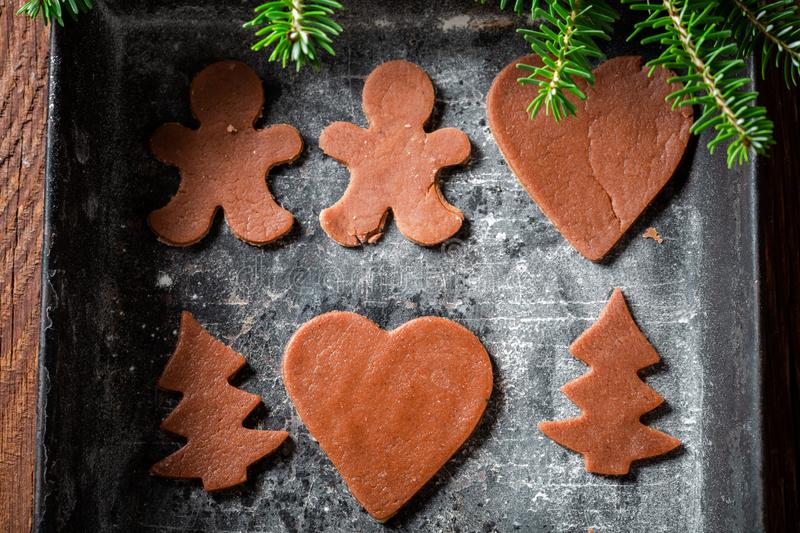 Brown Christmas gingerbread cookies in baking tray. On wooden table royalty free stock photography