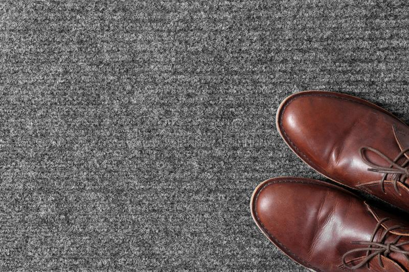 Brown classic shoes on gray doormat, top view. Space for text stock images