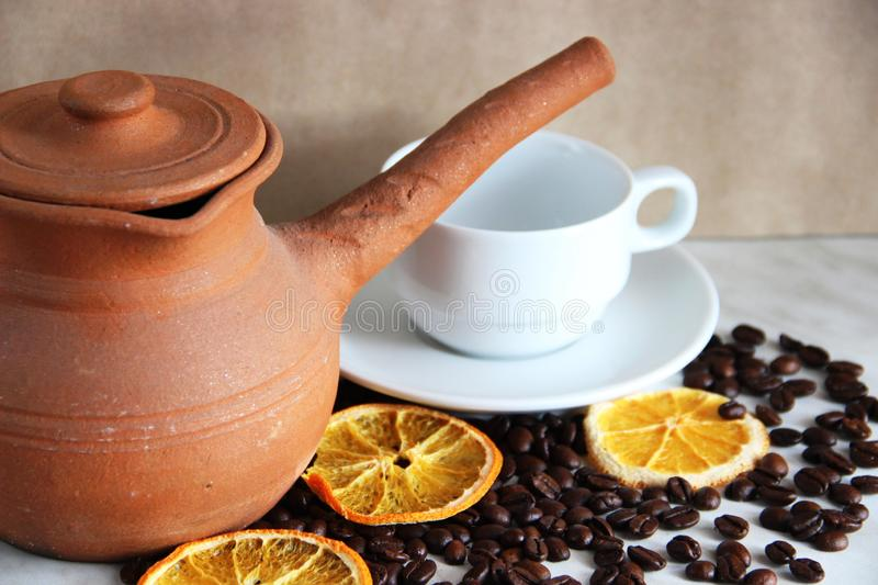 brown clay dishes, white clean Cup and saucer, lots roasted coffee beans and dried orange on the table royalty free stock images