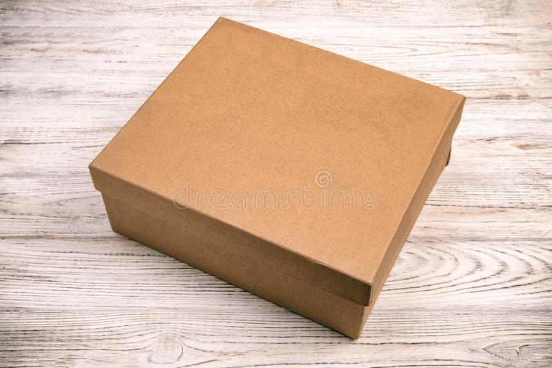 Brown closed cardboard box on a wooden background. top view vintage, toned, blank for you design stock photography