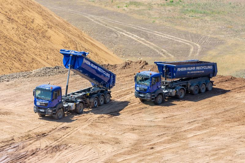 Brown coal open pit landscape with dumper trucks in Germany stock photo
