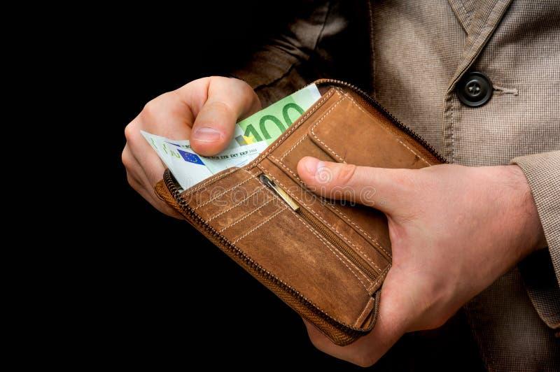 Brown cobre a carteira com euro- dinheiro nas mãos masculinas fotos de stock