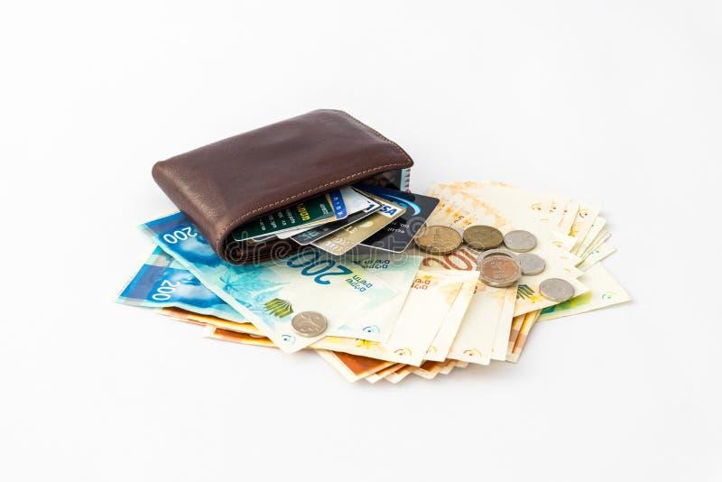 Brown cobre a carteira e os diversos cartões de crédito, os cartões do clube, a pilha de cédulas e as diversas moedas de shekels  fotos de stock royalty free