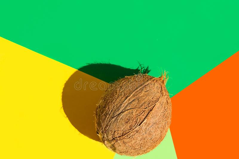 Brown coconut on multicolored graphic orange yellow green background. Hard light harsh shadows. Creative food poster. Healthy oil. For skin body care stock photography