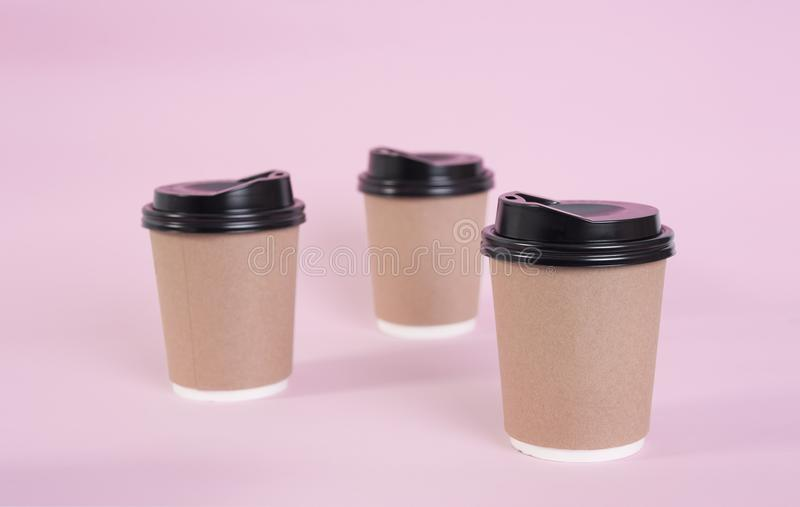 Brown coffee paper cup on pink background. mock up for branding royalty free stock photography