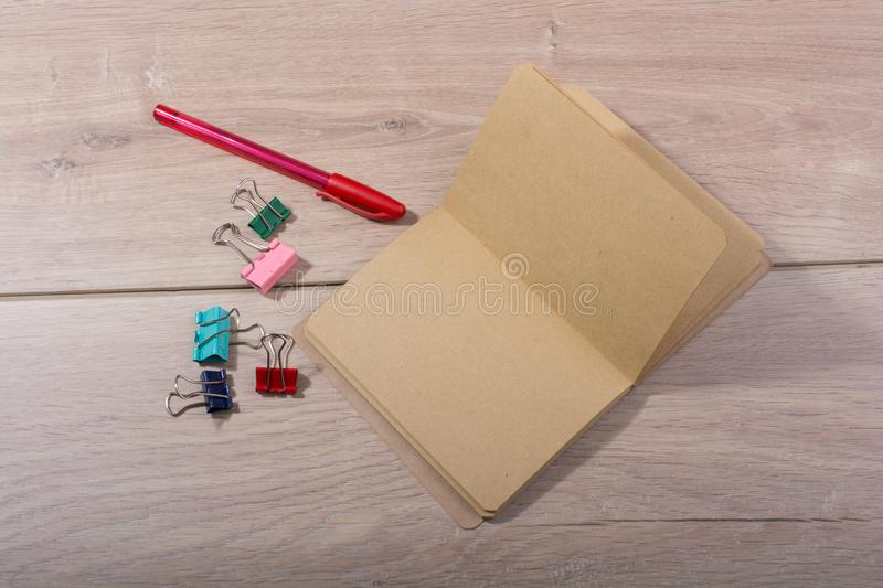 Brown color notebook , pen and paper clips. On wooden texture stock photography