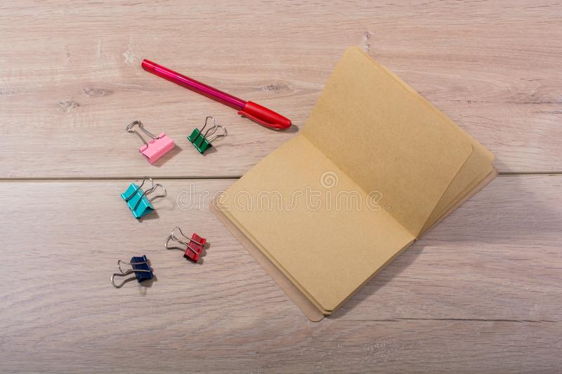 Brown color notebook , pen and paper clips. On wooden texture stock image