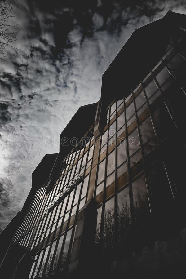 Brown Concrete Building With Glass Window Under Gray Sky royalty free stock images