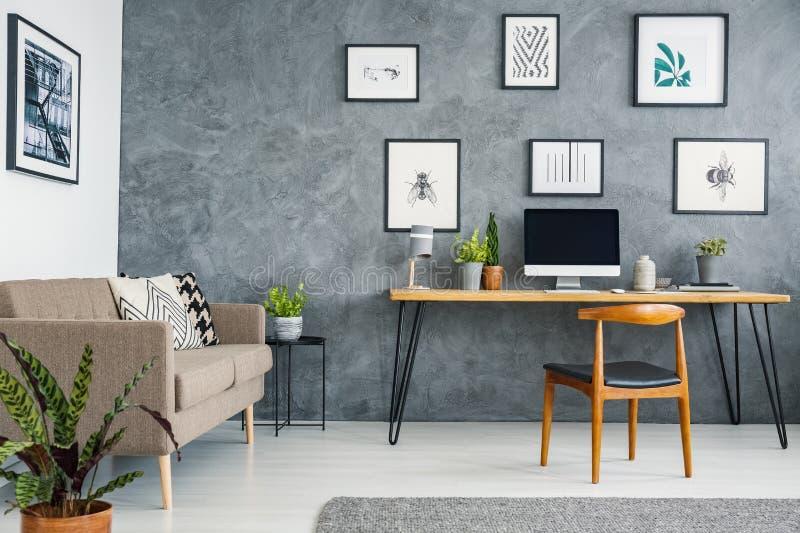 Brown-Couch nahe bei hölzernem Schreibtisch und Stuhl in grauem Freiberufler ` s I stockbild