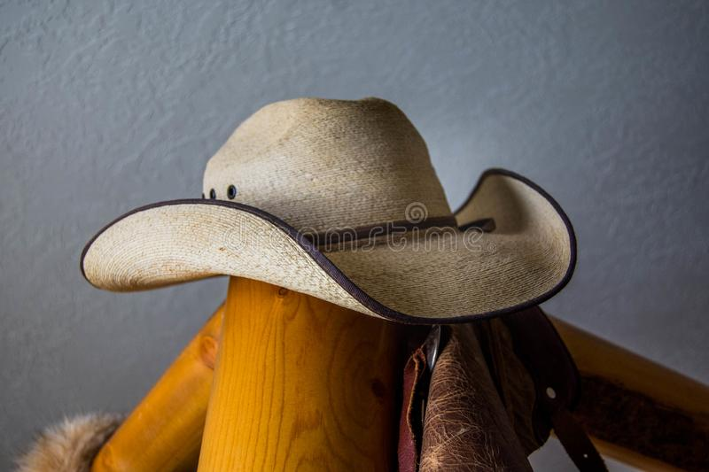 Brown straw cowboy hat sitting on a wood post bed frame. Brown cowboy hat perched on a wood pine pole bed frame stock photo