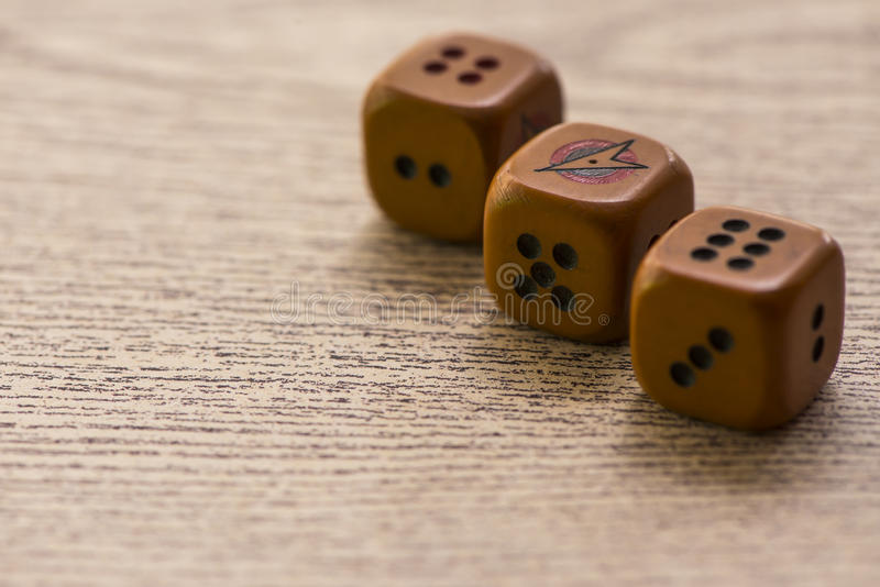 Brown dices on wooden background. stock photos