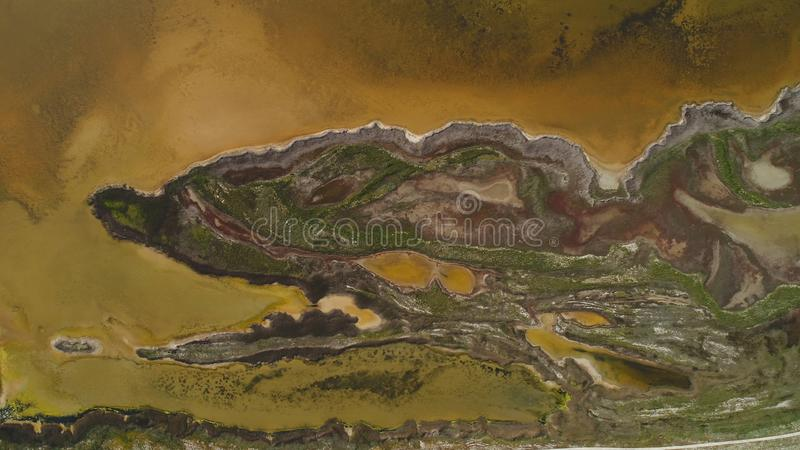 Brown dirty lake with patterned shore. Shot. Top view of patterned surface of marshy shores and musty brown acid lake royalty free stock photo