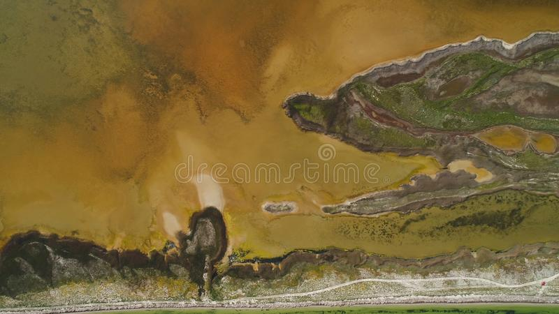 Brown dirty lake with patterned shore. Shot. Top view of patterned surface of marshy shores and musty brown acid lake stock photo