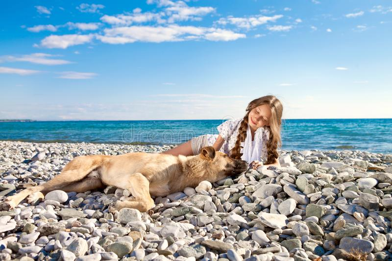 A brown dog and a girl are resting on the beach. Girl and dog stock photos