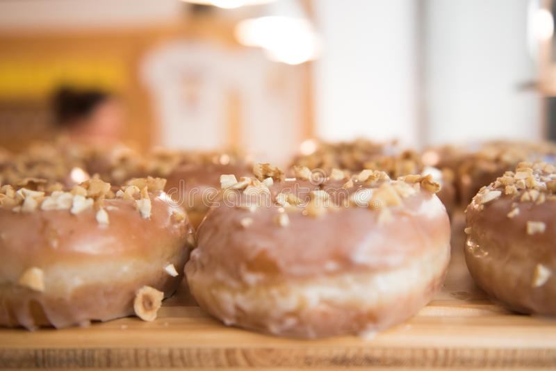 Brown donuts on a wooden plate. Close up. White background stock photography