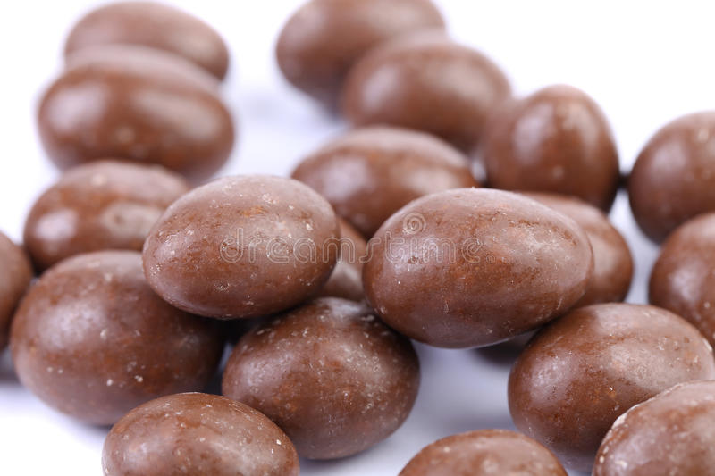 Brown dragee, in chocolate covered. White background. Close up stock image