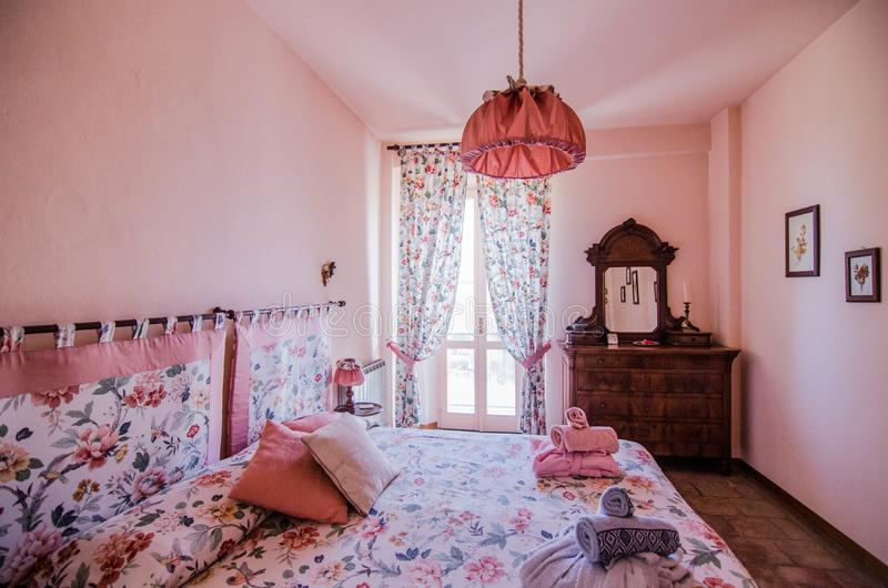 Brown dresser with mirror in pink room with curtained windows near flower patterned bed with pillows royalty free stock images