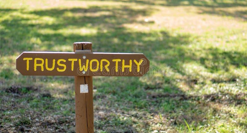 Brown drewniany podpisuje wewnątrz trawiastego pole z godny zaufania pisać na nim obraz royalty free