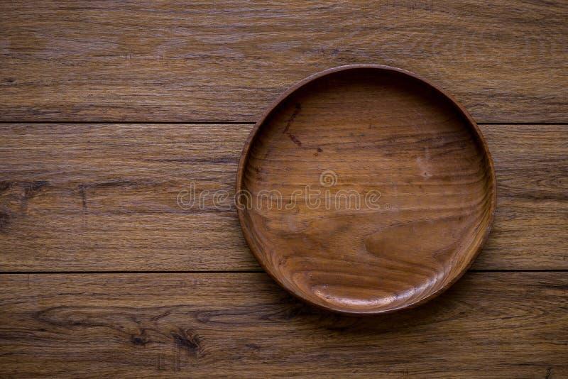Brown drewniany talerz na nieociosanym stołowym zbliżeniu horyzontalny wierzchołek obrazy stock