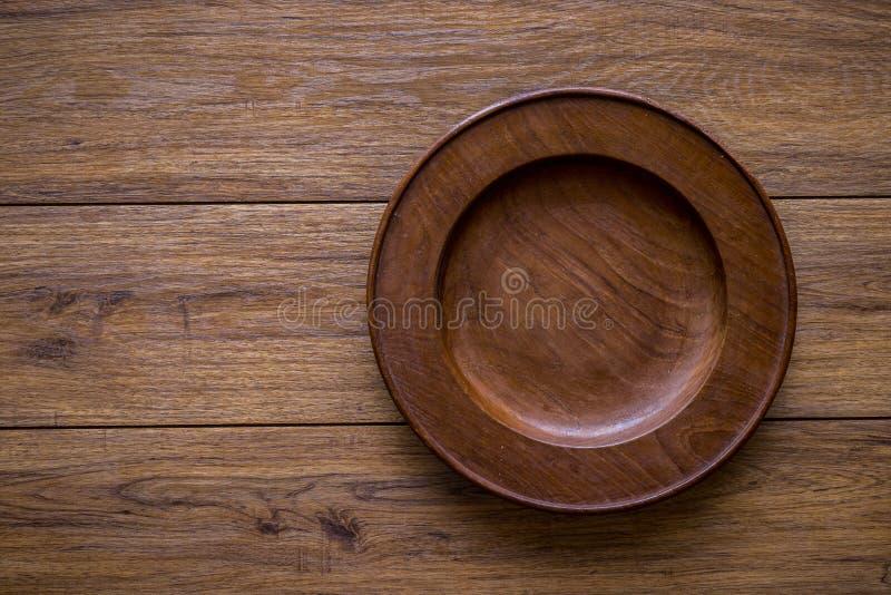 Brown drewniany talerz na nieociosanym stołowym zbliżeniu horyzontalny wierzchołek obrazy royalty free