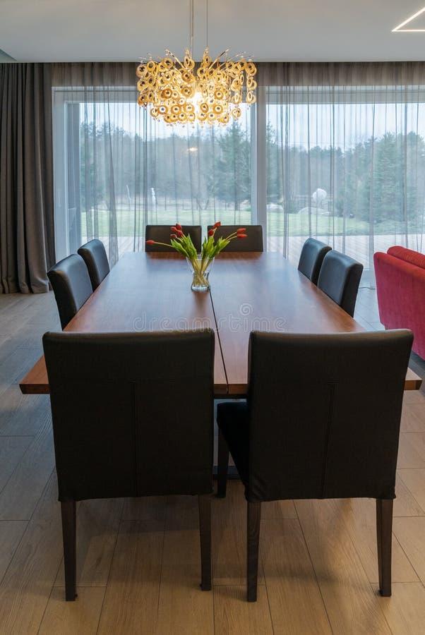 Brown drewniany wielki łomota stół z krzesłami w przestronnym, jaskrawym żywym pokoju w intymnym domu, zdjęcia stock