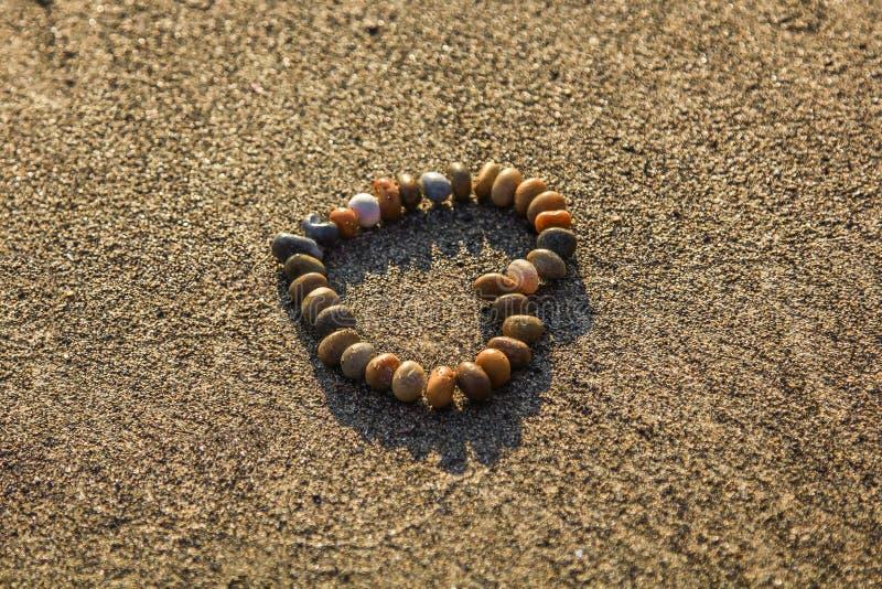 Brown e Grey Stone Formed Heart na areia imagem de stock