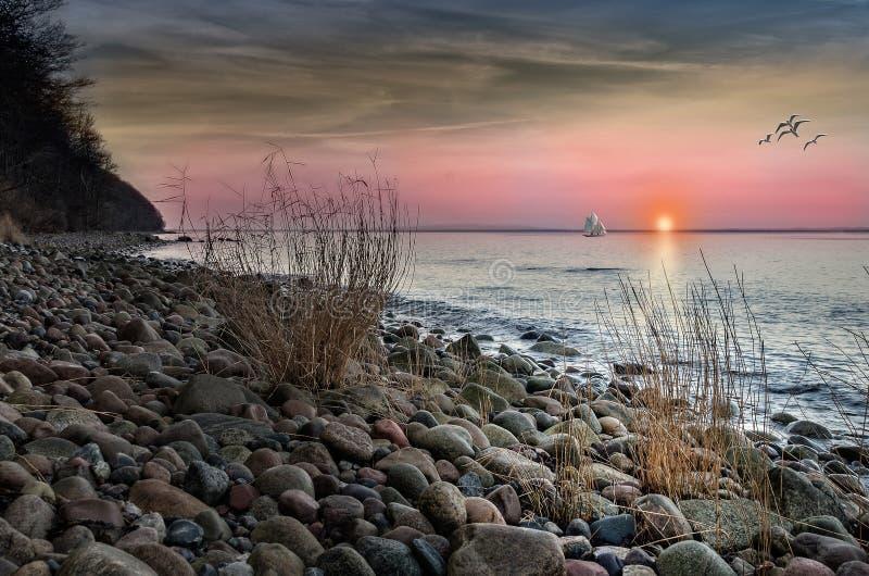 Brown e Grey Stones no litoral durante o por do sol foto de stock