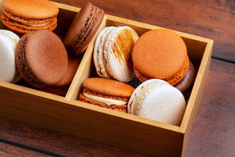 Brown e macarons ou bolinhos de amêndoa franceses brancos, chocolate, café, caramelo salgado e baunilha empilhados em uma caixa d foto de stock royalty free